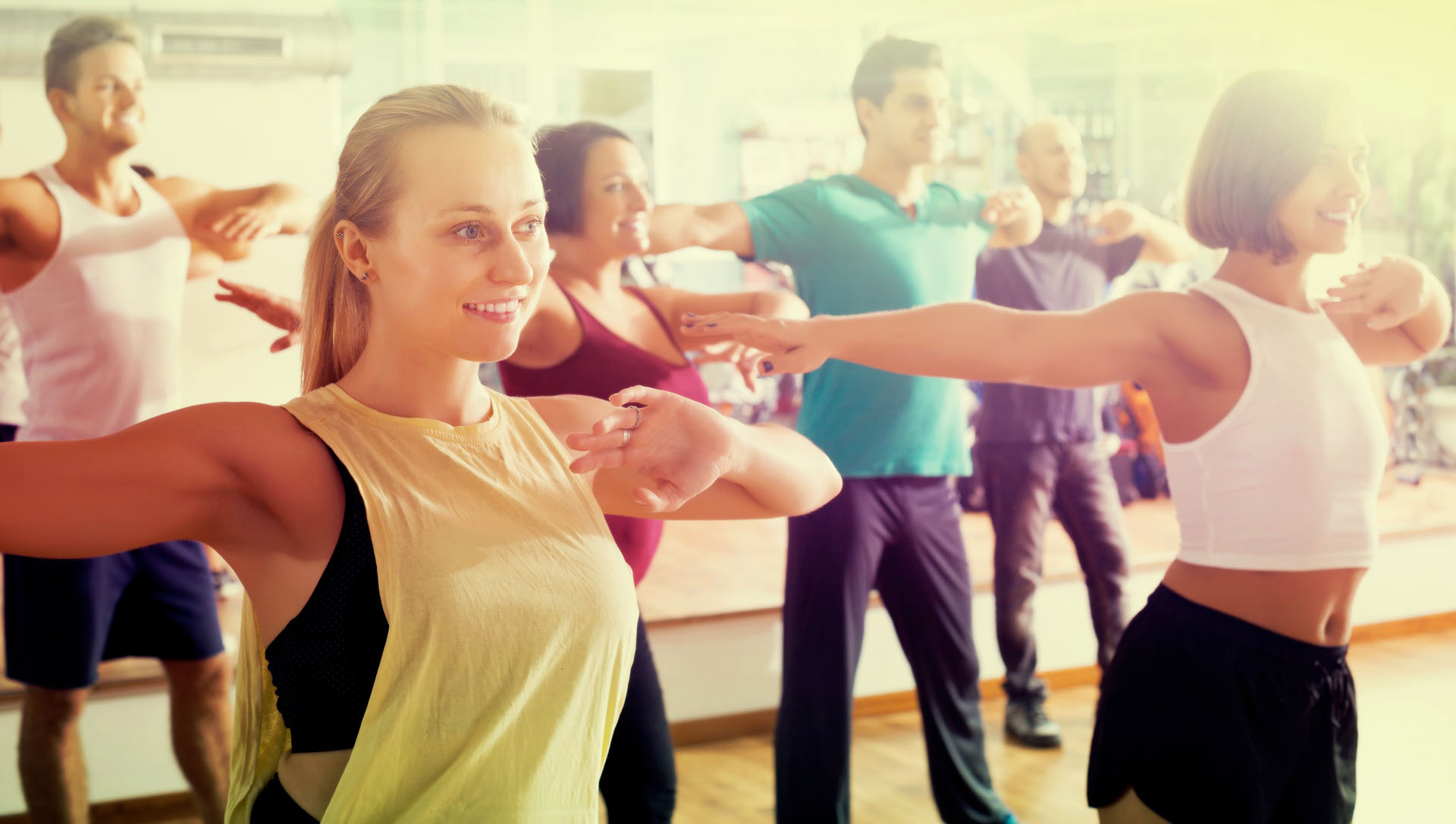 Portrait of positive men and ladies dancing zumba at lesson