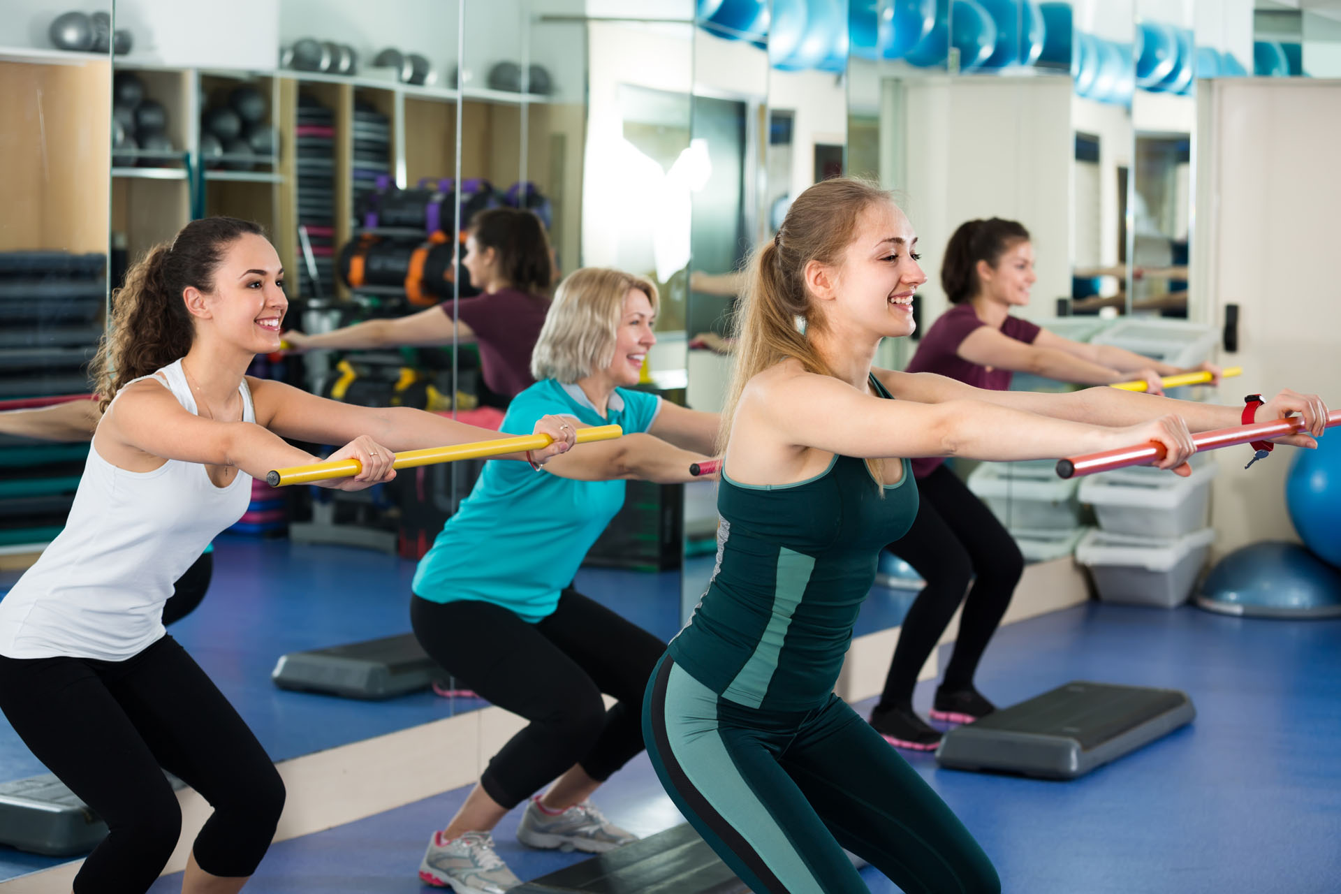 Positive different age women having group aerobic train in sport club . Selective focus