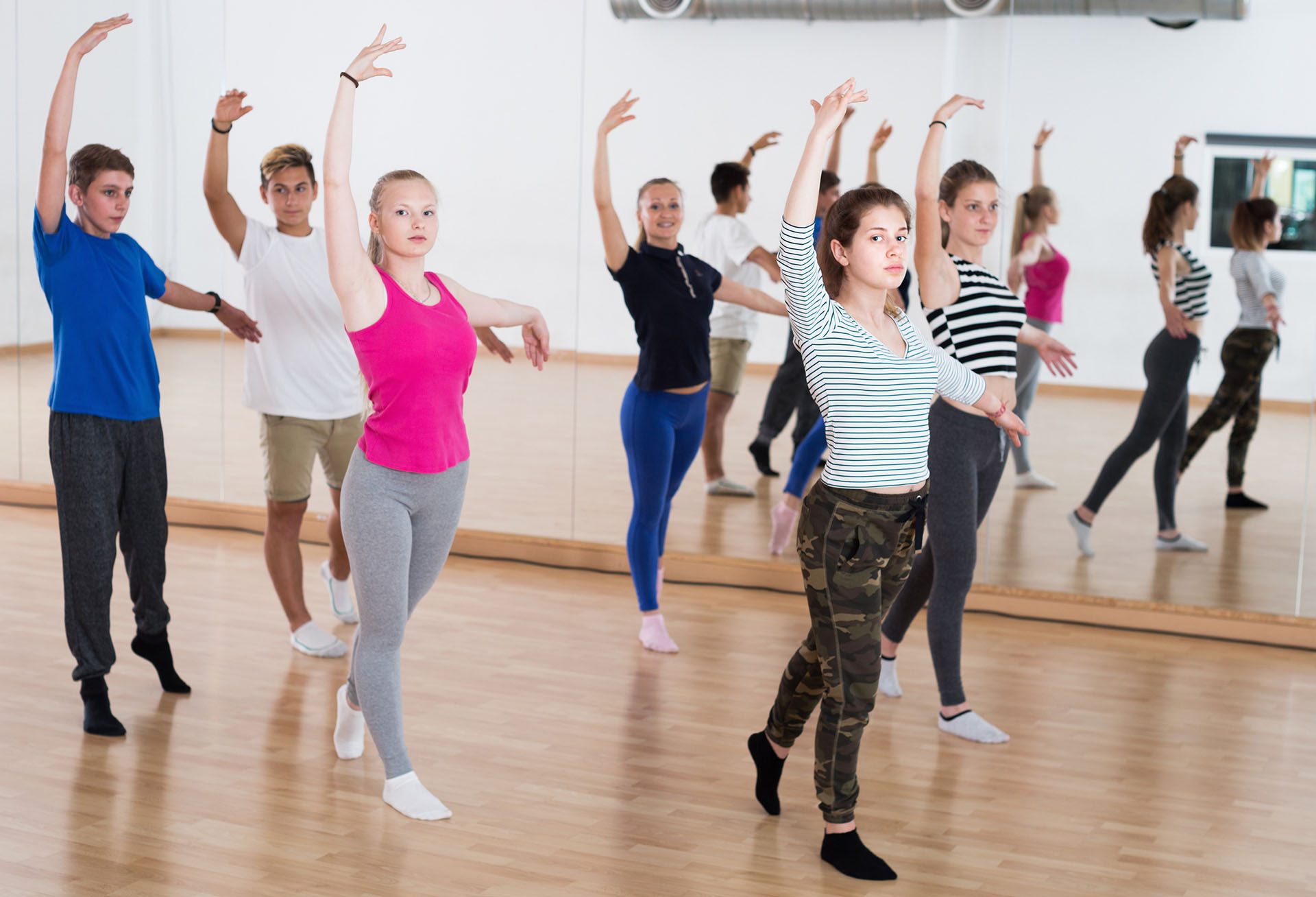 Smiling young ballet dancers exercising in ballroom