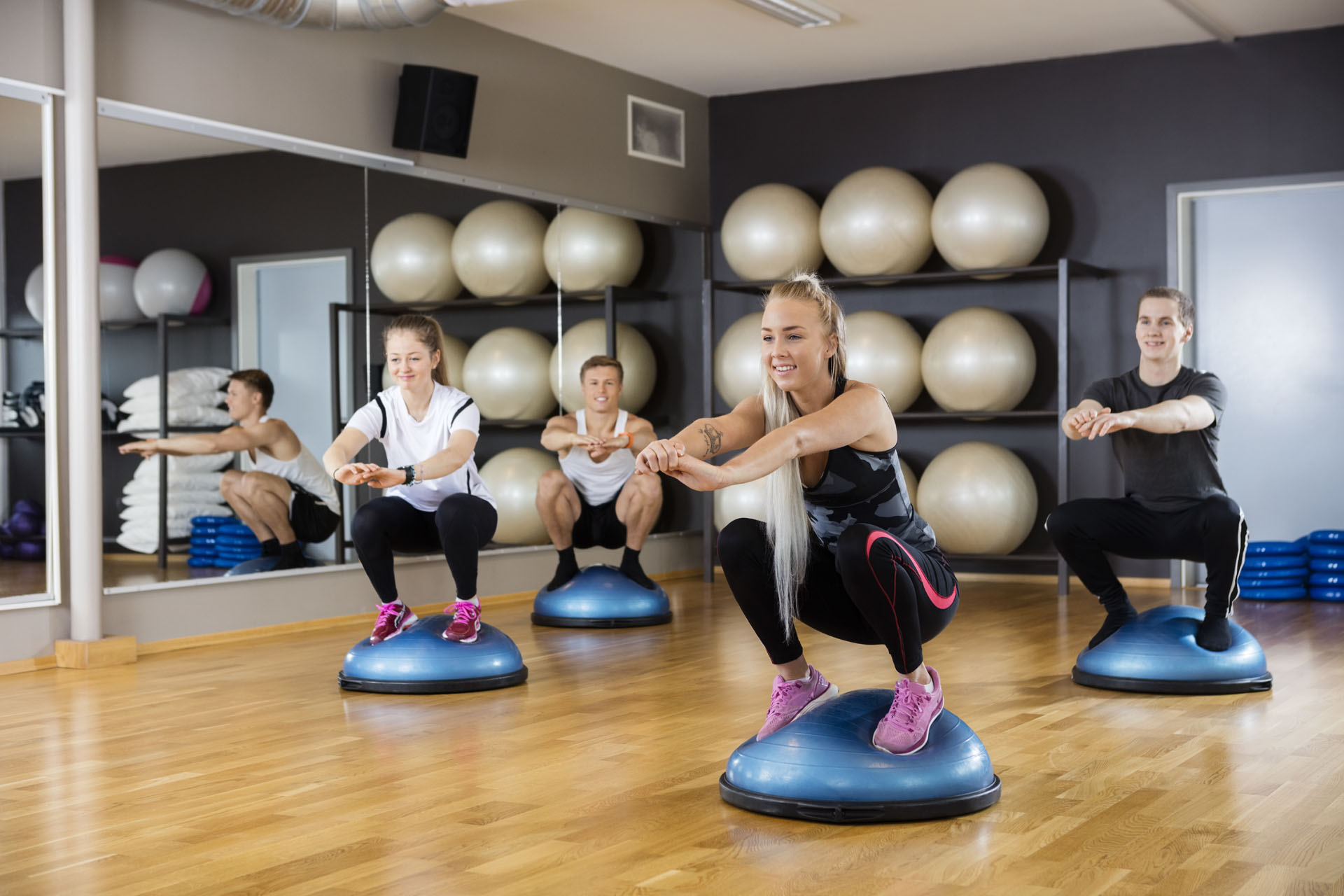 Male and female friends doing squatting exercise on bosu ball in gym