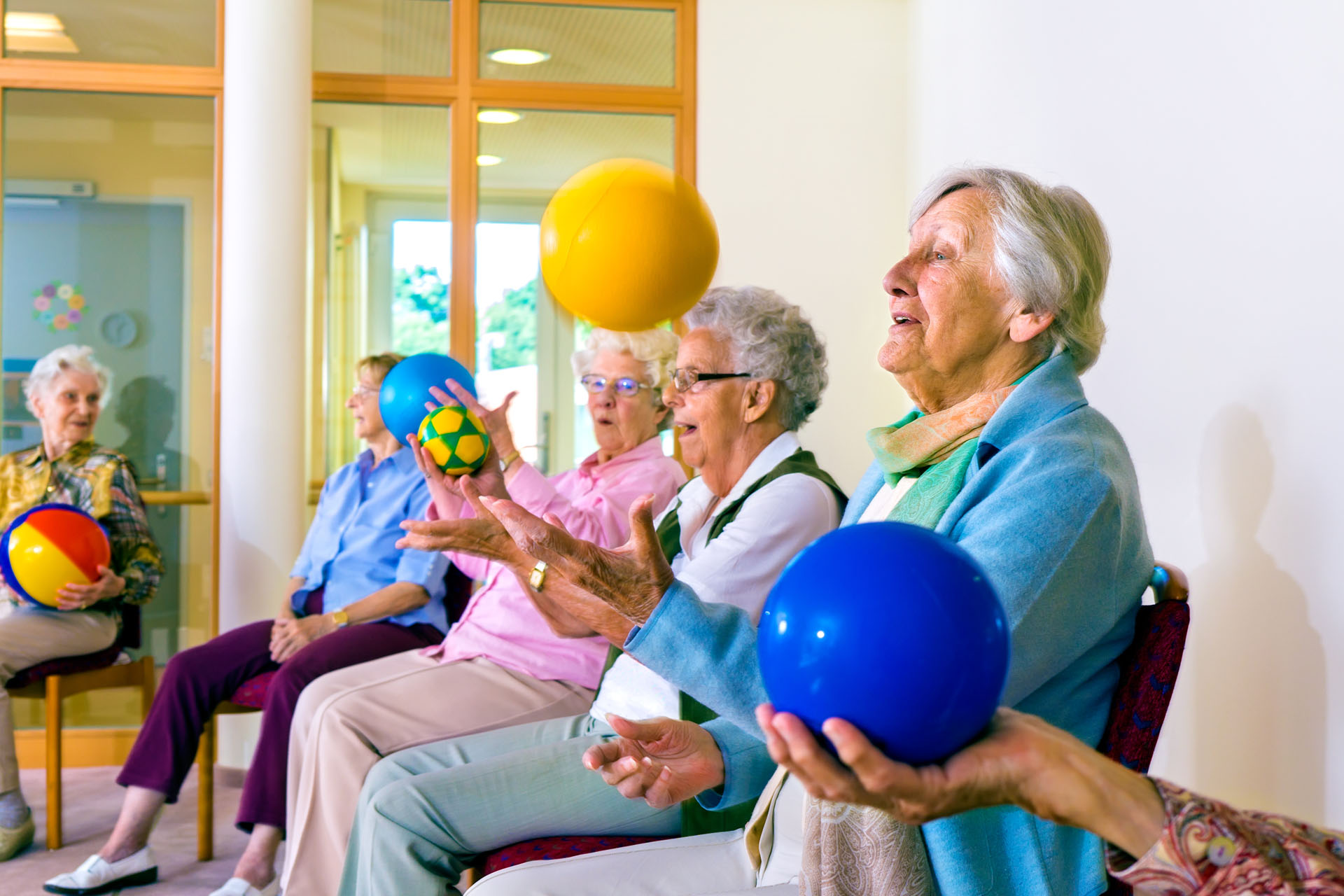 Group of happy senior ladies doing coordination exercises in a seniors gym sitting in chairs throwing and catching brightly colored balls.