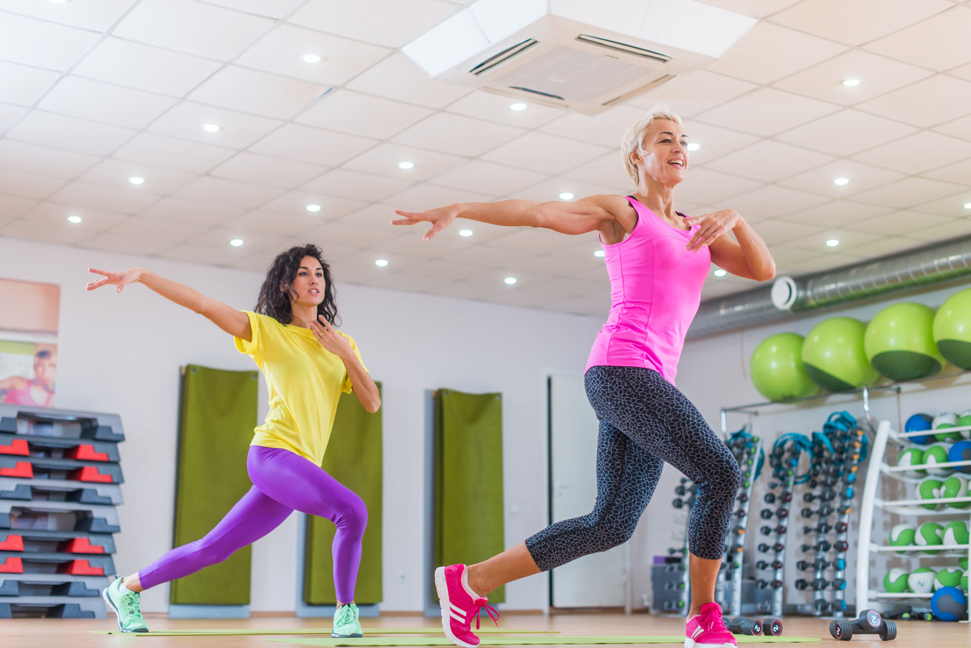 Two smiling female fitness models working out in gym or studio, doing cardio exercise, dancing zumba