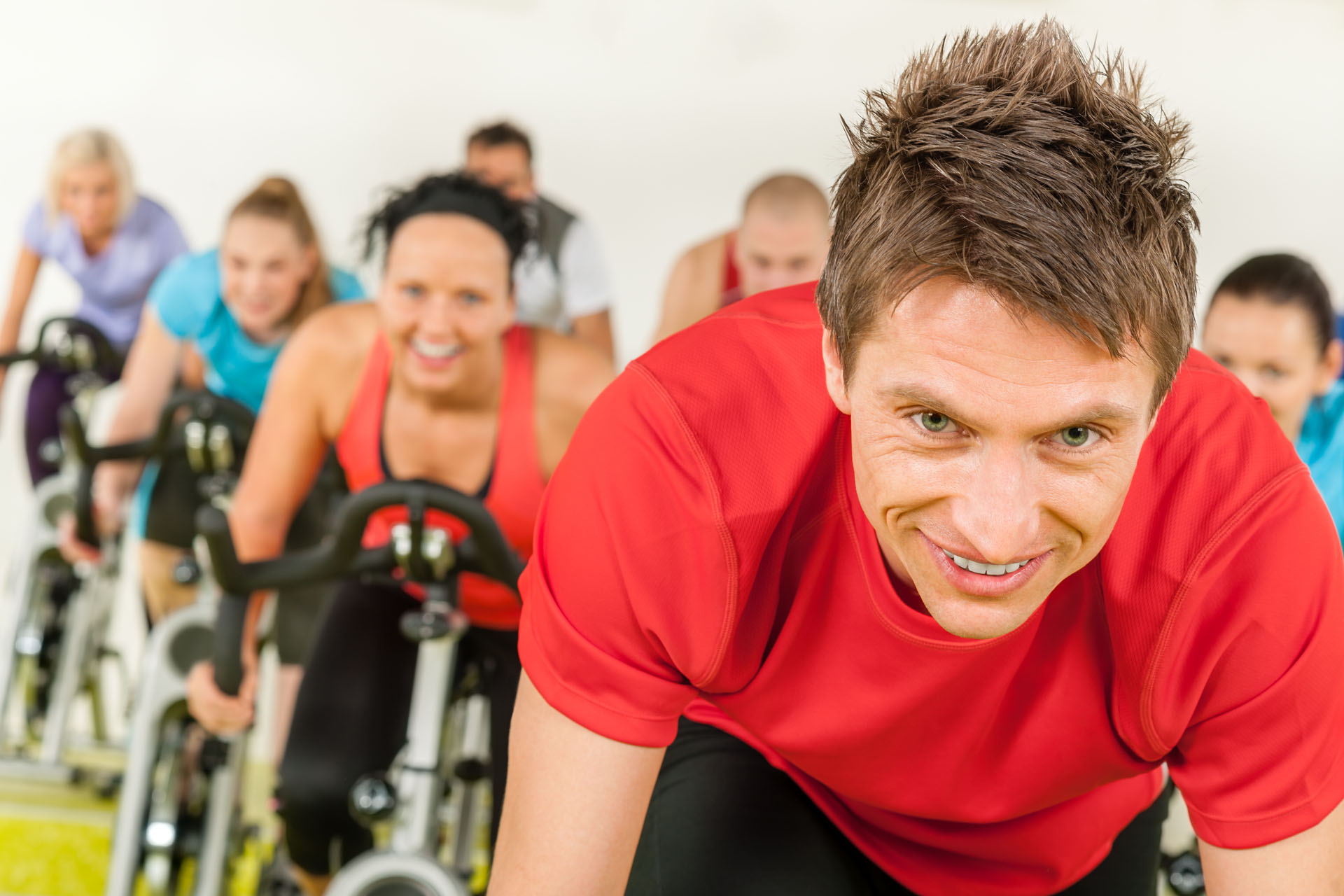 People spinning in gym or fitness club exercise cardio training