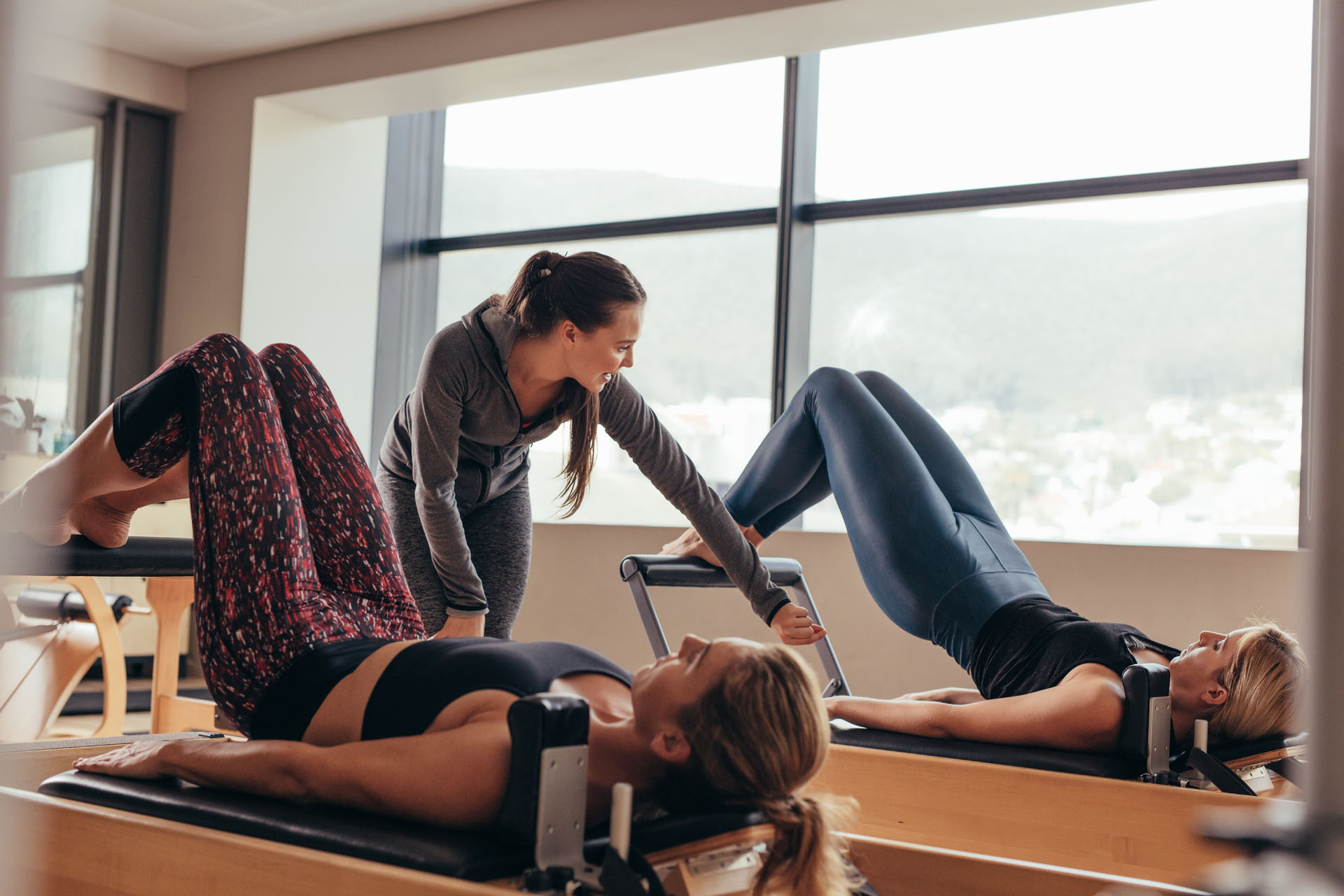 Women doing pilates exercises lying on machines while their trainer guides them. Two fitness women being trained by pilates instructor.