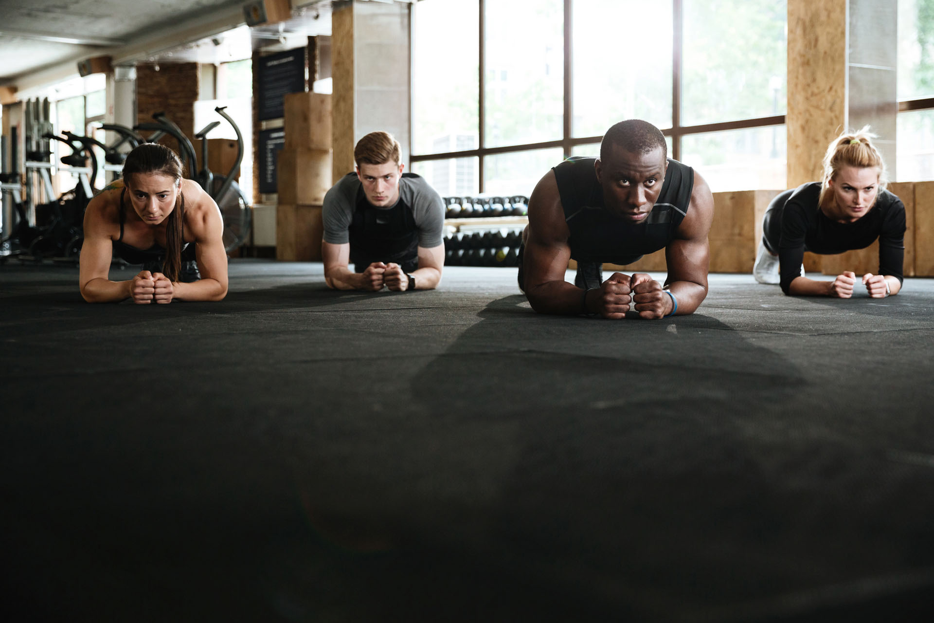 Picture of group of concentrated sports strong people make plank exercise. Looking aside.