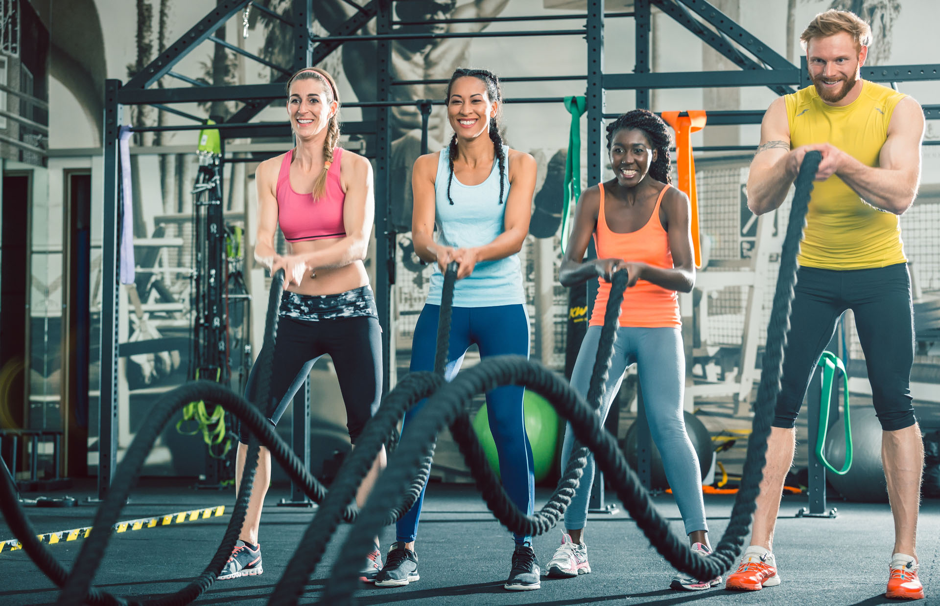 Determined and strong cheerful people exercising together with heavy battle ropes during intense functional training group class at a cool fitness club with modern equipment