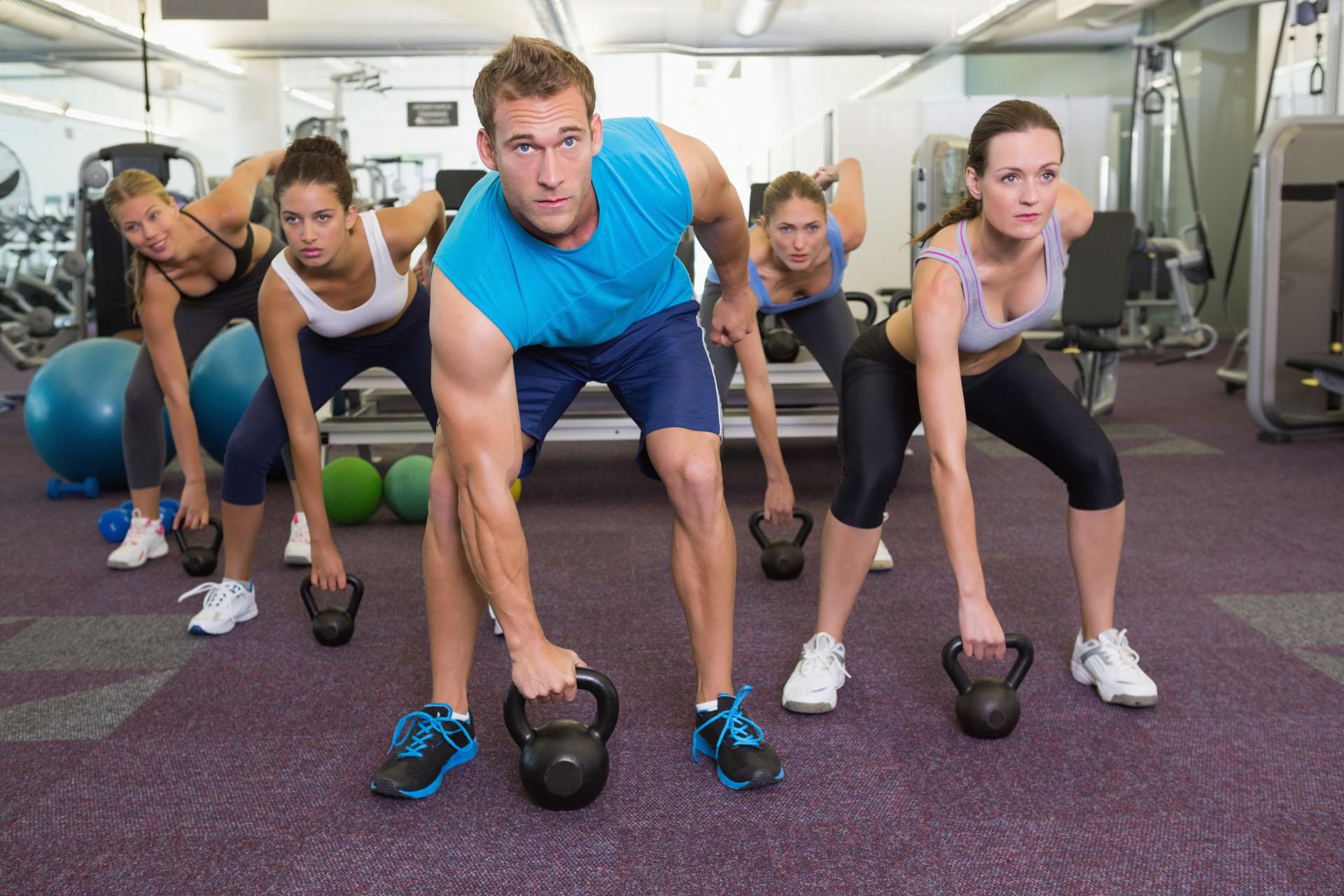 Muscular instructor leading kettlebell class