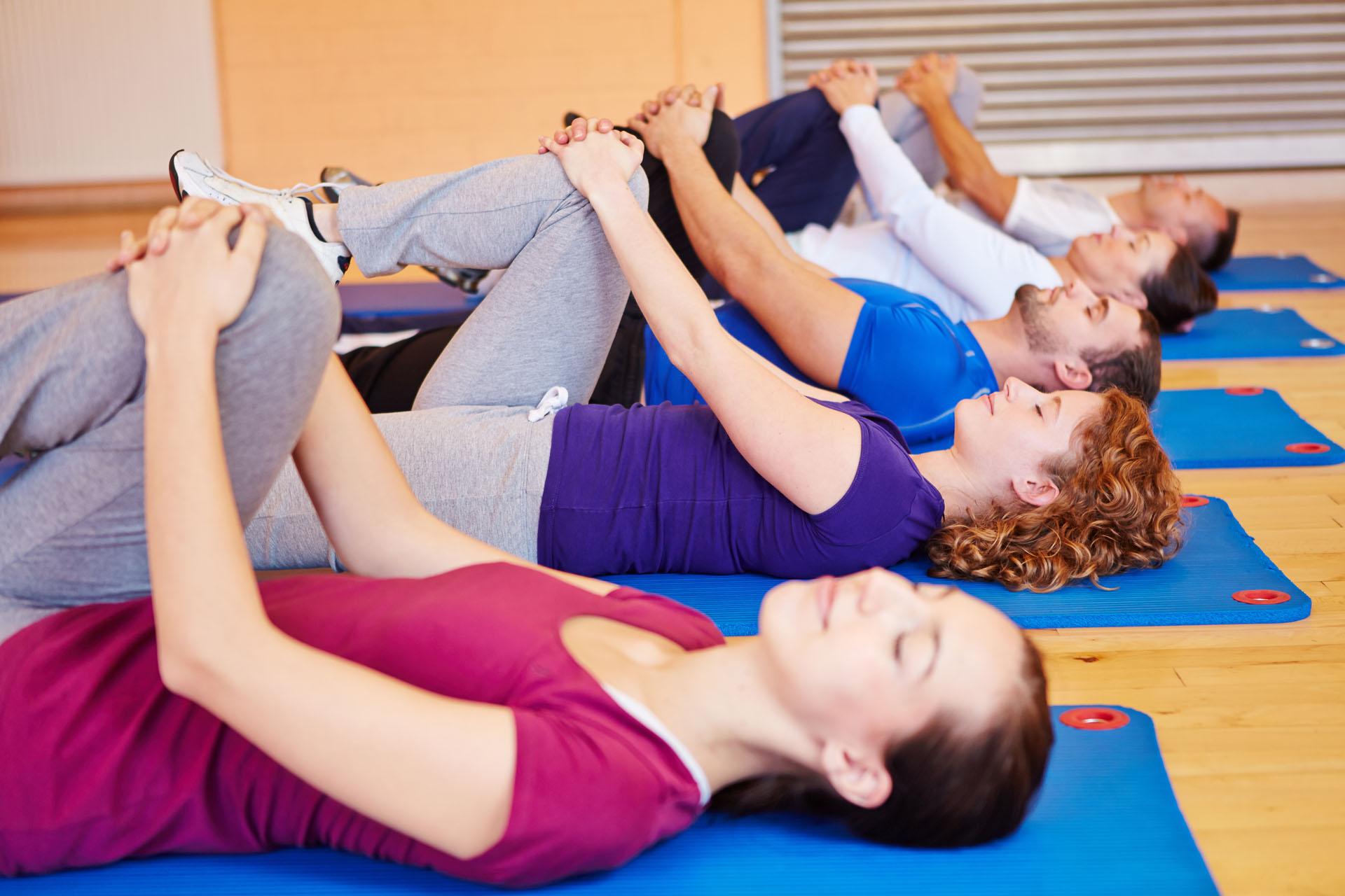 Gruppe liegt auf dem Rücken und macht Dehnübungen im Fitnesscenter