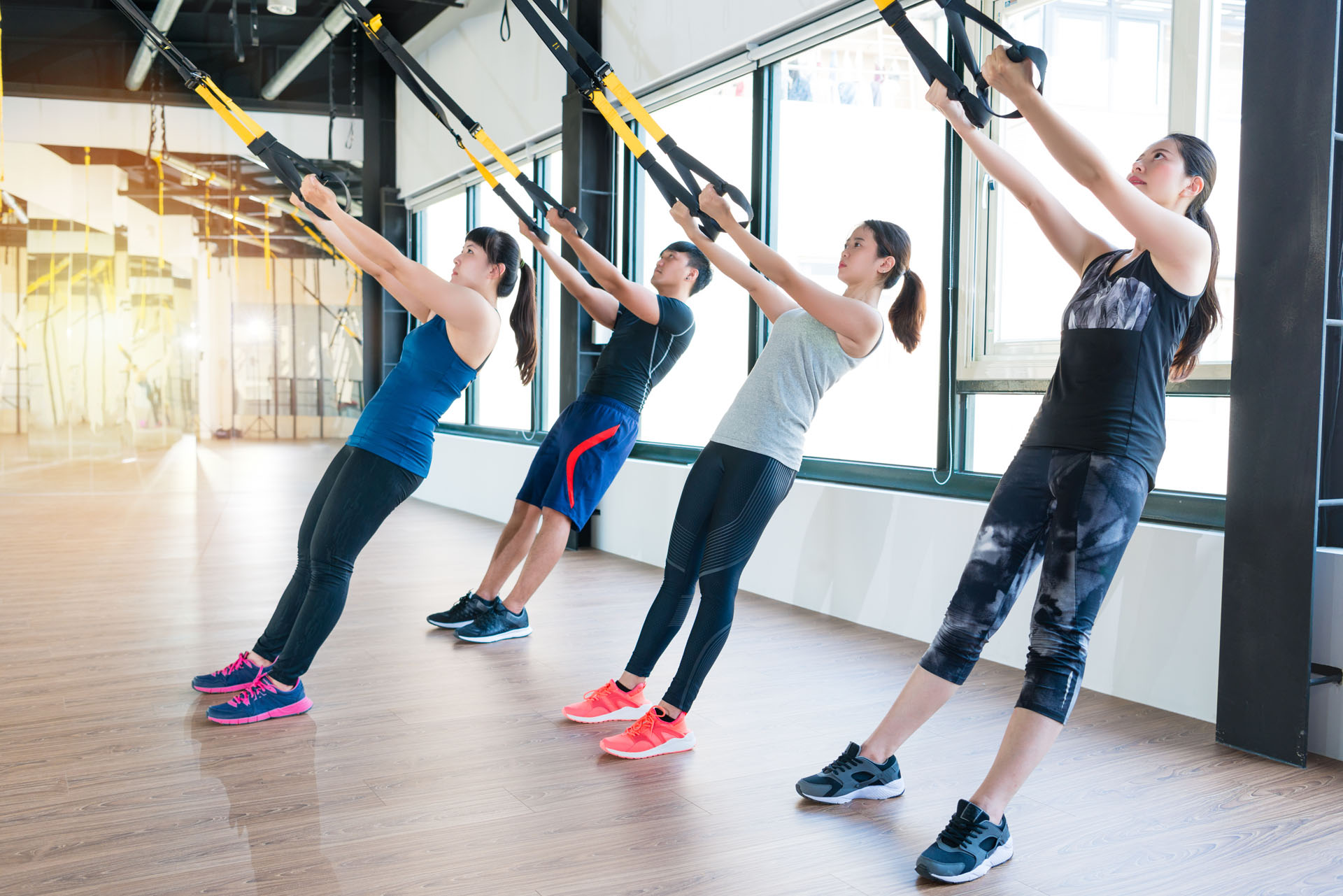group of fitness TRX suspension straps training exercises Asian people doing the pull up, working with own weight in a sunny bright gym.