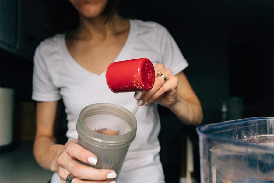 woman adding protein to smoothie