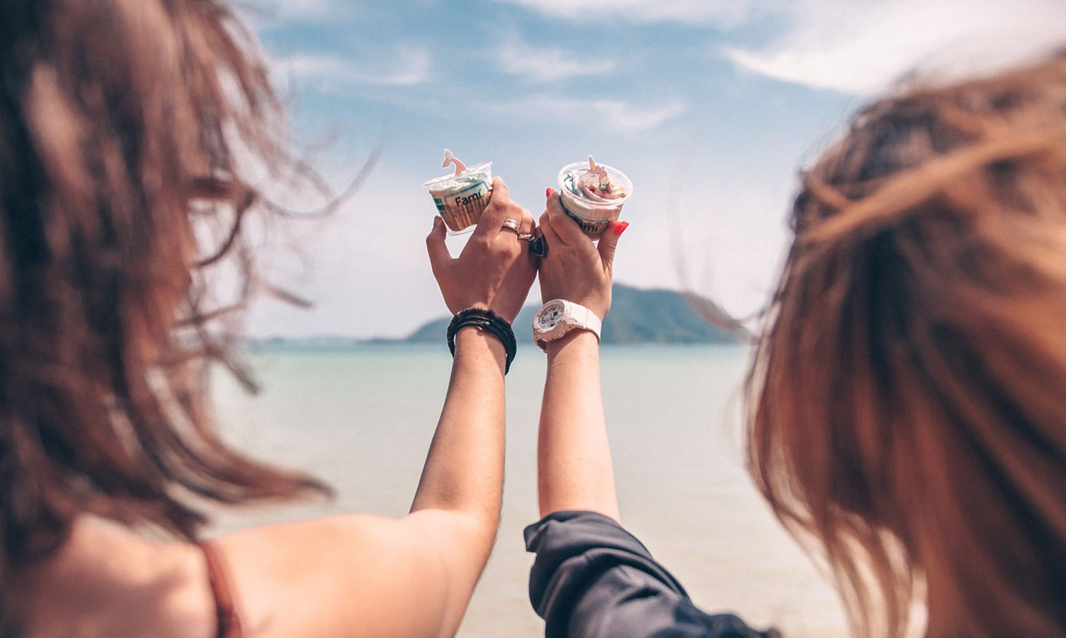 Women holding healthy snacks on the beach