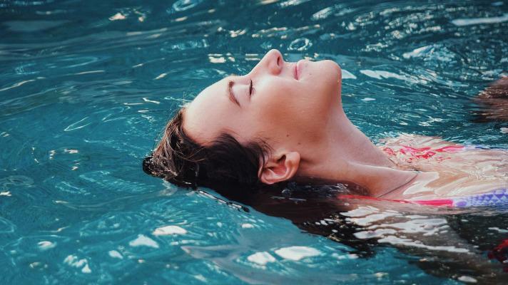 Woman doing backstroke in pool